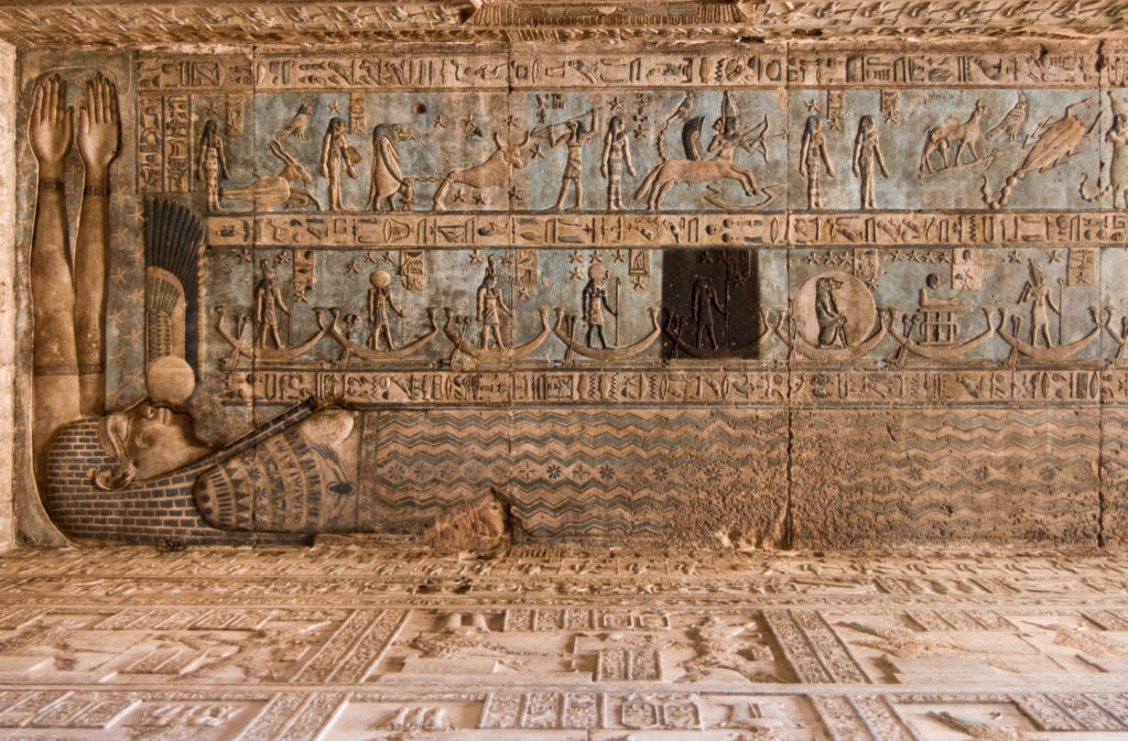 Ancient Egyptian ceiling at Dendera Temple.  Signs of the zodiac are carved and painted including Taurus the bull, Scorpio and Sagittarius.  The goddess of the sky - Nut - is holding them together in her arms.   Ancient sculpture, over 1000 years old.